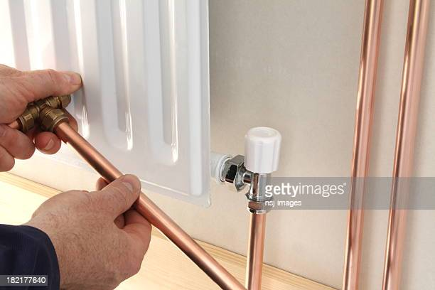 A plumber installing a new radiator