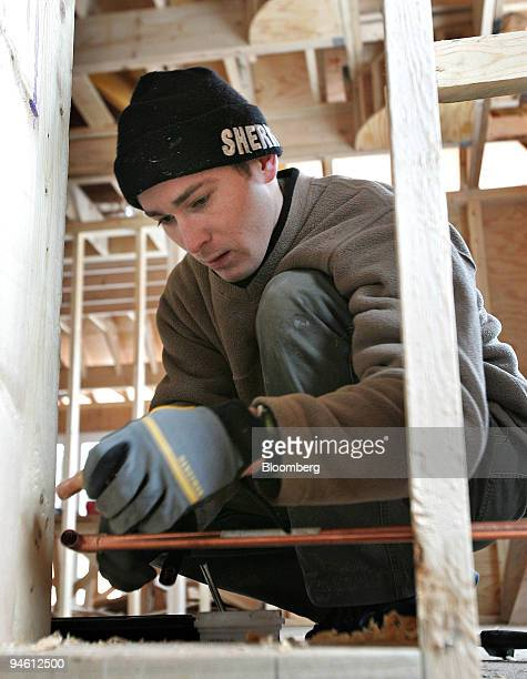 Plumber Jacek Ardo works in a new single-family home under construction March 1 in Park Ridge, Illinois. Construction spending in the U.S. Fell by...