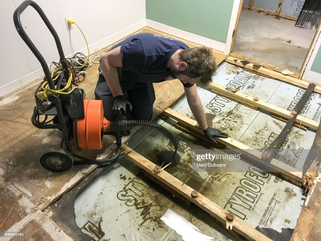 Plumber pushing a plunger drain into drain to unclog it : Stock Photo