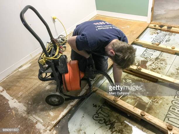 Plumber pushing a plunger drain into drain to unclog it