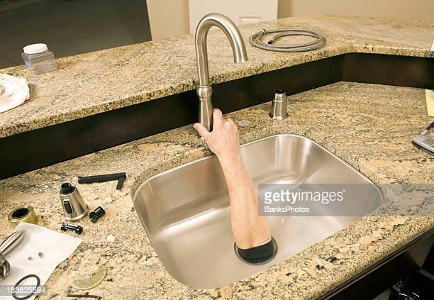Plumber Reaches Hand through Sink Drain to Attach Faucet