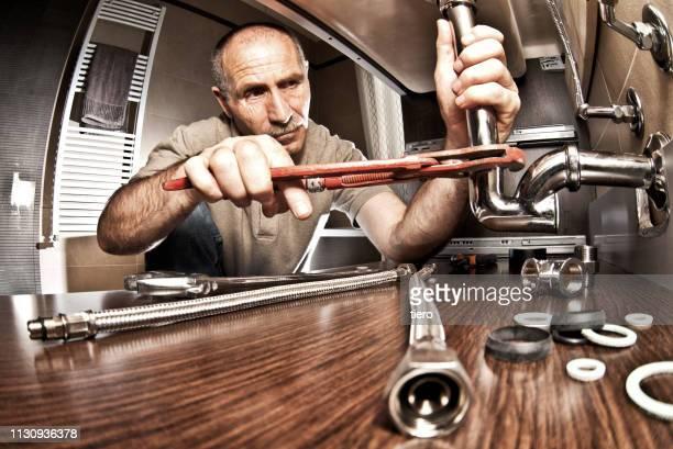 plumber repairing pipe - plumbing stock pictures, royalty-free photos & images