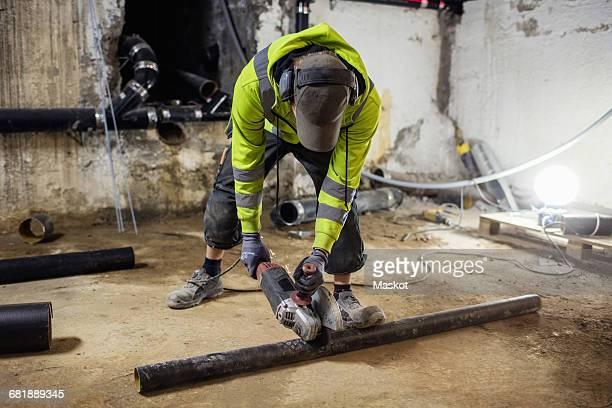 Plumber sawing pipe at illuminated basement