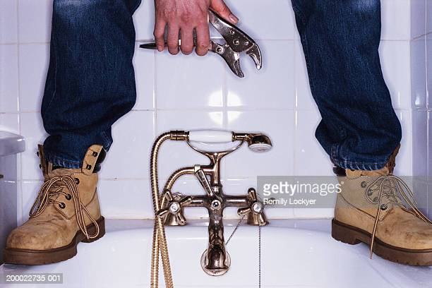 Plumber standing on bath, low section