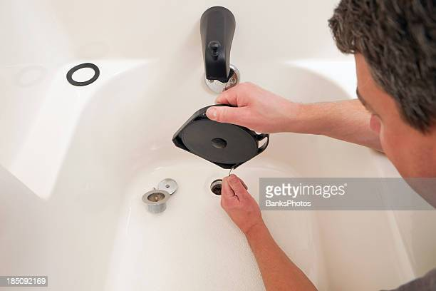 plumber  unclogging bathtub drain - clogs stock pictures, royalty-free photos & images