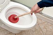 Plumber uncloging toilet