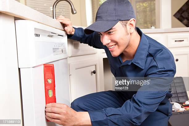 Plumber working on dishwasher in domestic kitchen