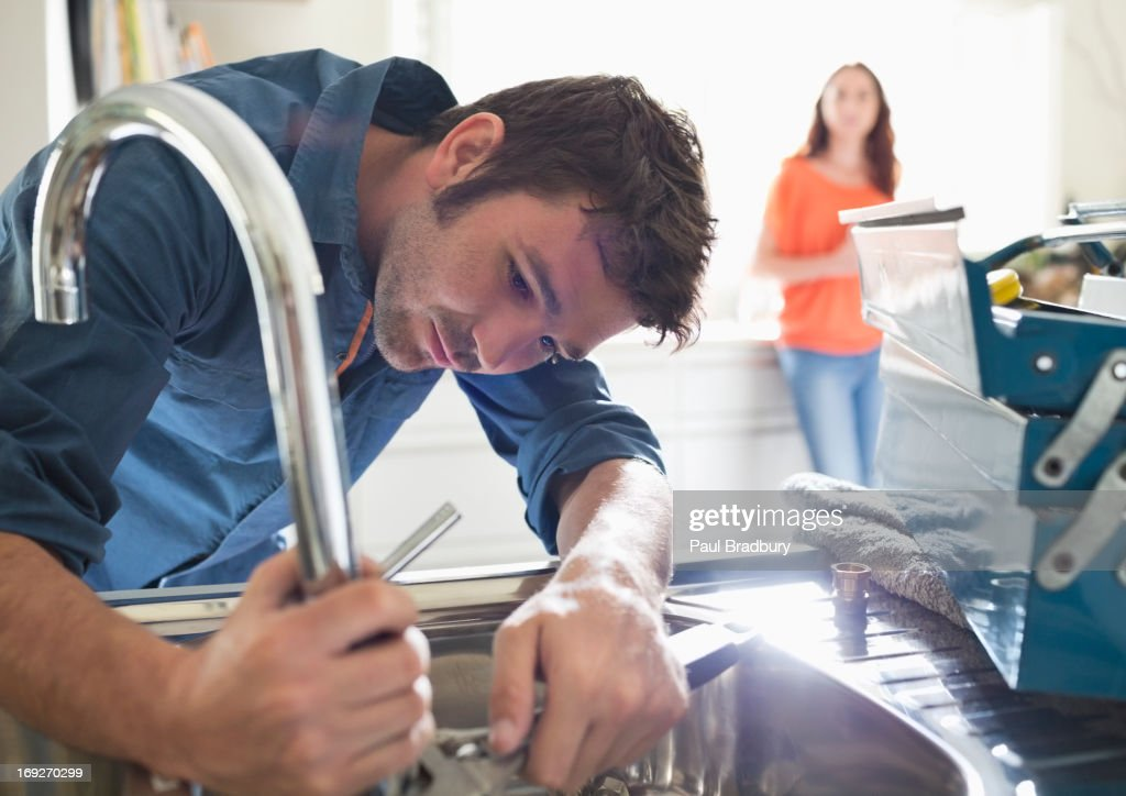 Plumber working on kitchen sink : Stock Photo