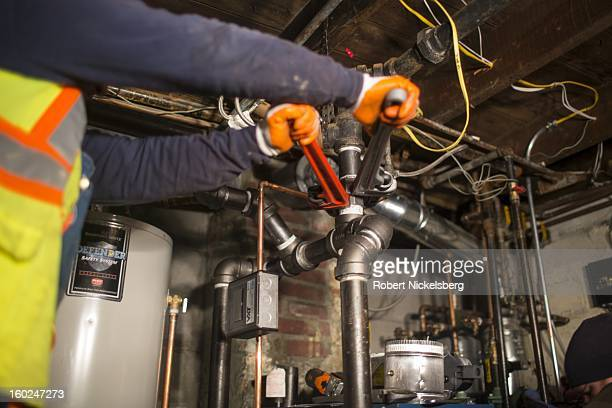 Plumbers install a new boiler in a basement at a private residence January 17, 2013 flooded during Hurricane Sandy in the Rockaways January 17, 2013...