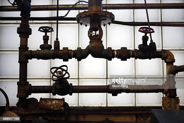 Plumbing stands next to tanks used to dye packages of raw wool at the Woolrich Inc woolen mill in Woolrich Pennsylvania US on Wednesday Nov 4 2015...