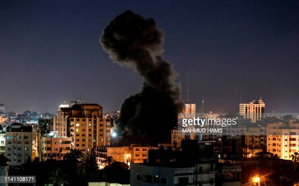 TOPSHOT A plume of smoke billows above buildings during an Israeli airstike on Gaza City on May 4 2019 Gaza militants fired a barrage of rockets at...