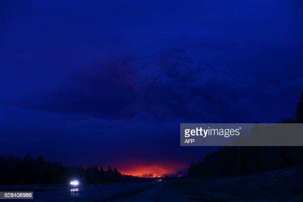 TOPSHOT A plume of smoke hangs in the air as forest fires rage on in the distance in Fort McMurray Alberta on May 4 2016 Numerous vehicles can be...
