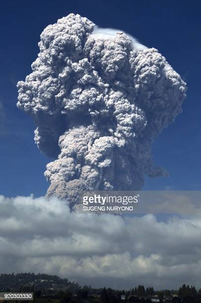 A plume of think volcanic ash hangs in the air from Mount Sinabung volcano taken from the city of Berastagi in North Sumatra on February 19 2018...
