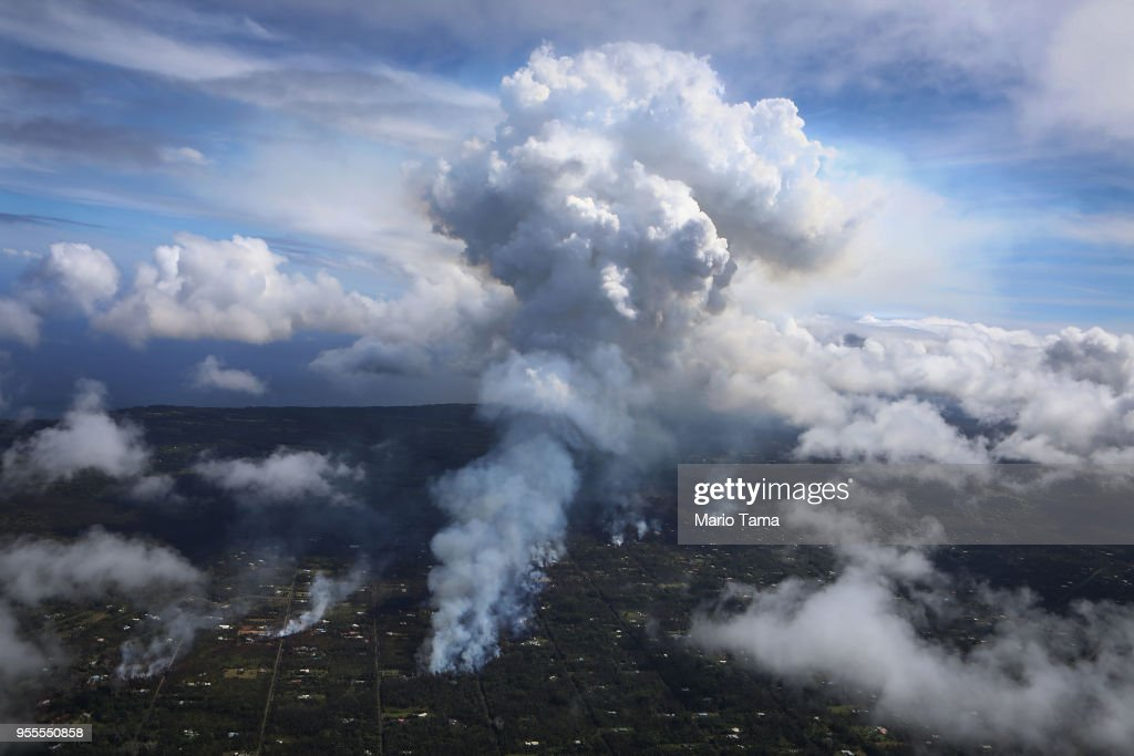 A plume of volcanic gas mixed with smoke from fires caused by lava rises (C) amidst clouds in the Leilani Estates neighborhood in the aftermath of eruptions from the Kilauea volcano on Hawaii's Big Island on May 6, 2018 in Pahoa, Hawaii. A magnitude 6.9 earthquake struck the island May 4. The volcano has spewed lava and high levels of sulfur dioxide gas into communities, leading officials to order 1,700 to evacuate. Officials have confirmed 26 homes have now been destroyed by lava in Leilani Estates.