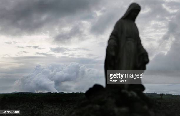 A plume of volcanic gases mixed with smoke from fires caused by lava rises from the vicinity of the Leilani Estates neighborhood with a statue of the...
