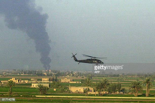 Plumes of black smoke are seen from a burning pipe line on the outskirts of the restive city of Fallujah 50 kms west of Baghdad 10 November 2004...