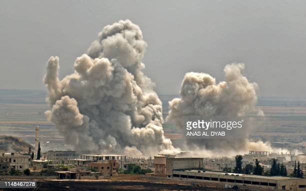 TOPSHOT Plumes of smoke rise following reported Syrian government forces' bombardment on the town of Khan Sheikhun in the southern countryside of the...