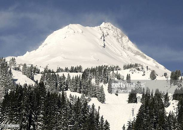 Plumes of winddriven powder billow over Oregon's Mount Hood on a powder day at Mount Hood Meadows ski area