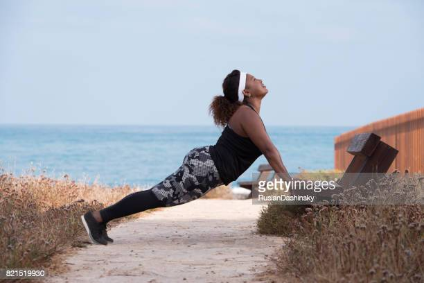 Plump woman doing back stretching exercise on the bench outdoors.