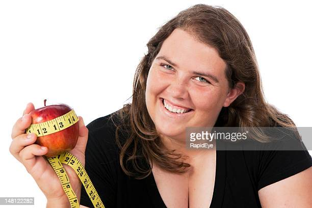 Plump  woman holds apple wrapped in tape measure and smiles