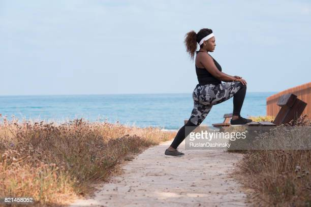 Plump woman stretching her legs on the bench outdoors.