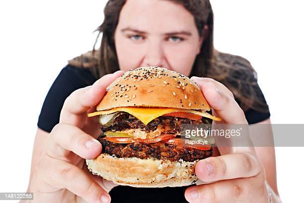 weiche junge frau über zum verstauen in nahaufnahme cheeseburger - schlechte angewohnheit stock-fotos und bilder