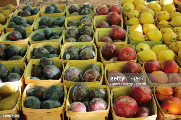 Plums And Apples Arranged In Boxes At Market For Sale
