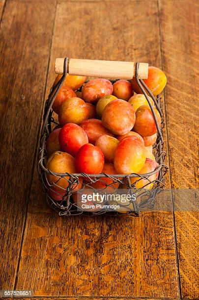 plums in a wire basket - claire plumridge stock pictures, royalty-free photos & images