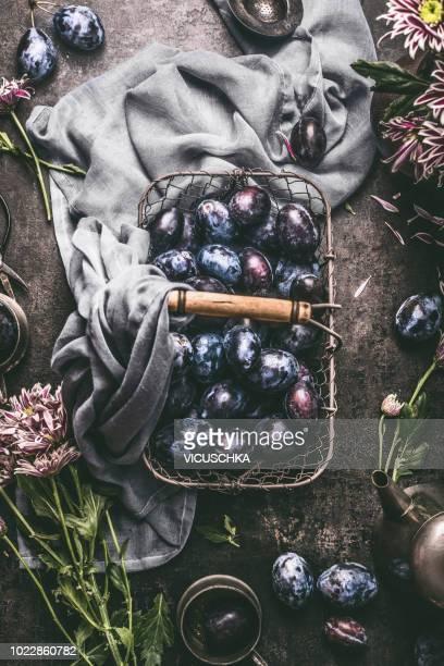 Plums in basket on dark rustic table.