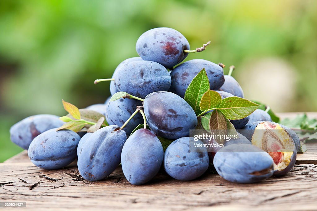 Plums on an old wooden table. : Stock Photo