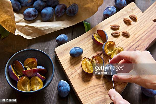 Plums on chopping board, pitting