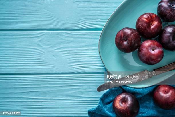ciruelas crudas frutas rojas de ciruela frutas de verano en madera azul - ciruela fotografías e imágenes de stock