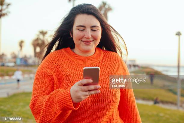 plus size girl texting outdoors - femme pulpeuse photos et images de collection