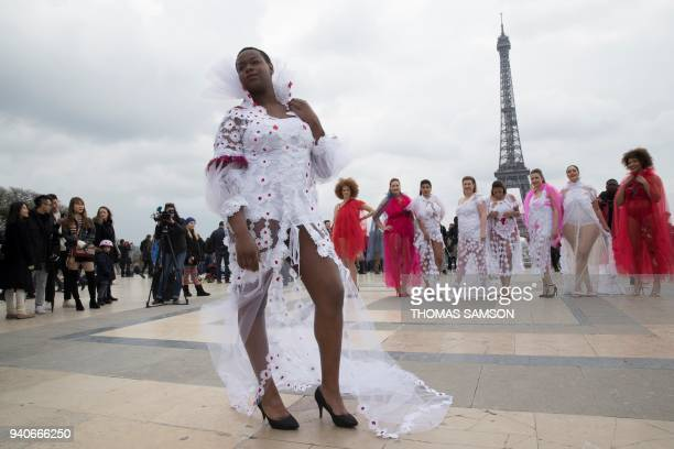 TOPSHOT Plus size models pose in front of the Eiffel Tower in Paris on April 1 during an happening as part of the 'All Sizes Catwalk' event aiming at...