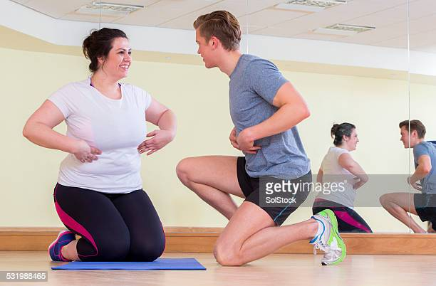 Plus Size Woman Exercising With A Trainer