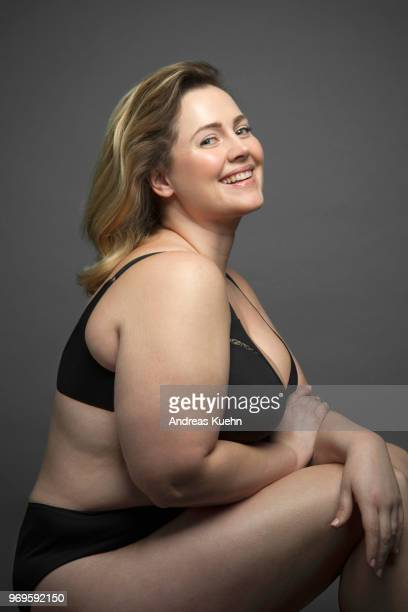 Plus size woman in her mid thirties with a big smile wearing black lingerie.