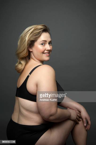 Plus size woman in her thirties wearing only black lingerie sitting in front of a dark gray background while looking over her shoulder with a big smile.