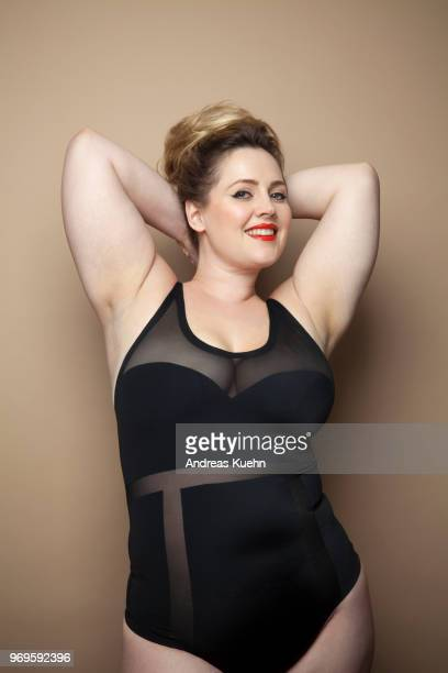 Plus size woman in her thirties with a big smile, red lipstick and an up do wearing a lingerie bodysuit with her arms up behind her head.