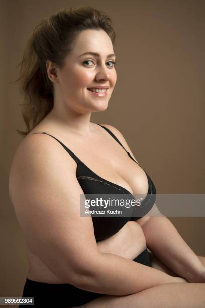 Plus size woman in her thirties with a big smile sitting down wearing black lingerie.