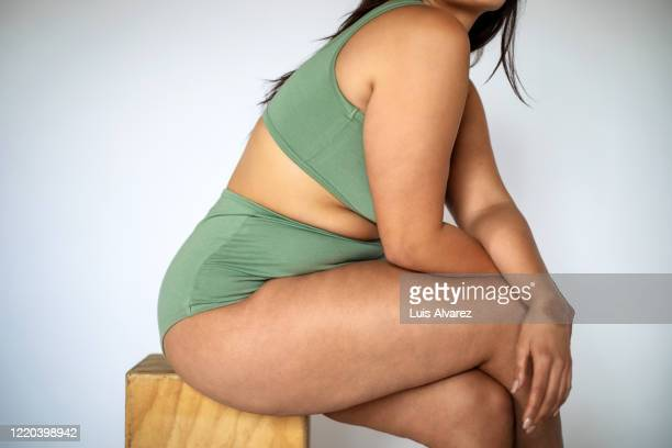 plus size woman in lingerie sitting on a stool - body positive stock pictures, royalty-free photos & images