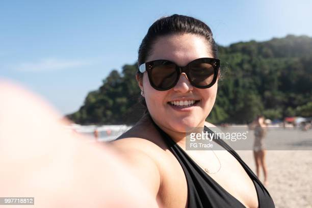 plus size femme prenant un selfie à la plage - femme pulpeuse photos et images de collection