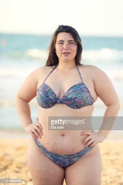 plus size woman wearing bikini standing at beach - estrias fotografías e imágenes de stock