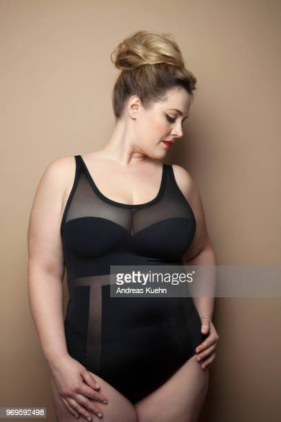 Plus size woman with red lipstick wearing an up do and a lingerie bodysuit.