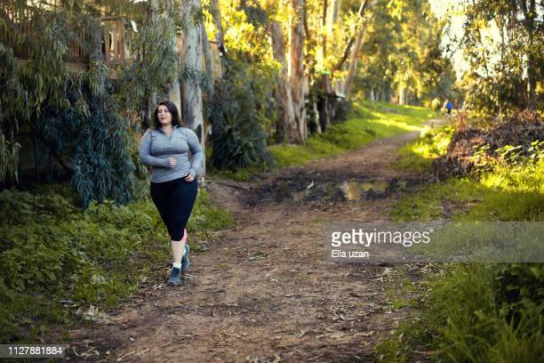 plus size women jogging and exercising at the park - curvy women stock pictures, royalty-free photos & images