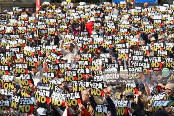 Plusieurs milliers de manifestants défilant dans la rue contre le premier ministre Shinzo Abe et son gouvernement portant des panneaux 'No Abe...