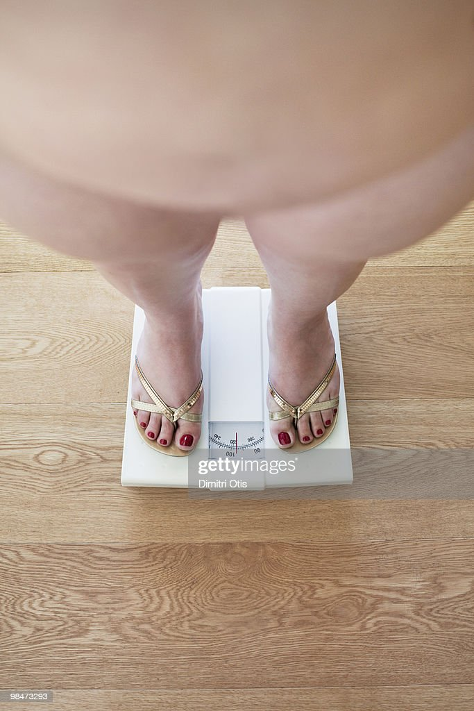 Plus-size woman on scale : Stock Photo