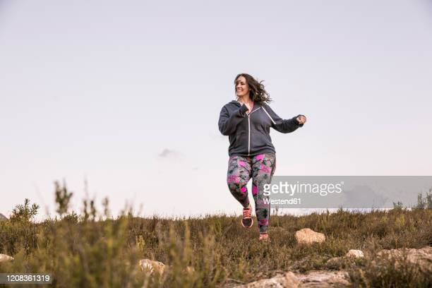 plus-size-model jogging in the countryside - 30代の女性だけ ストックフォトと画像