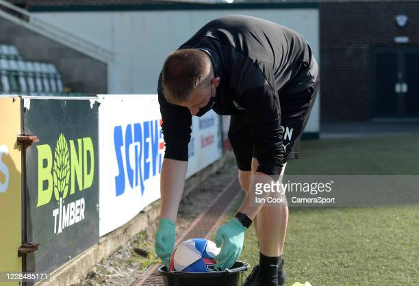 Plymouth Argyle ground staff member disinfects a match ball during the game during the Sky Bet League One match between Plymouth Argyle and Blackpool...