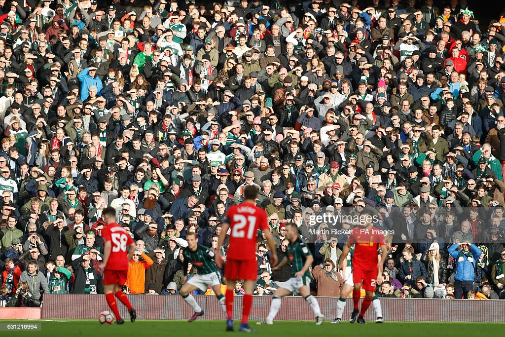Plymouth Argyle supporters shield their eyes from the sun as they watch from the stands during the Emirates FA Cup, Third Round match at Anfield, Liverpool.