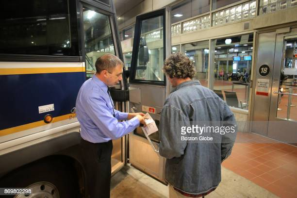 Plymouth Brockton bus driver Stoyan Asenov checks a ticket before departing South Station in Boston on Nov 1 2017 With a shortage in the bus driver...